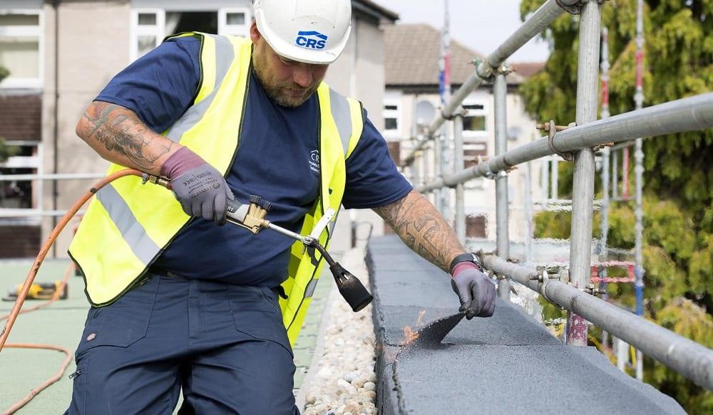 Roofer installing built-up felt